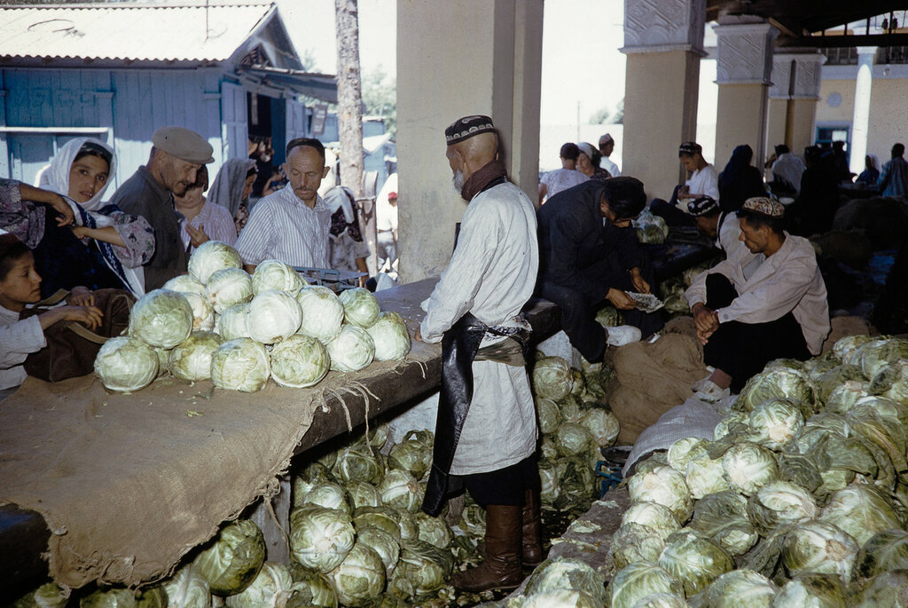 Uzbekistan, merchant selling cabbages at market