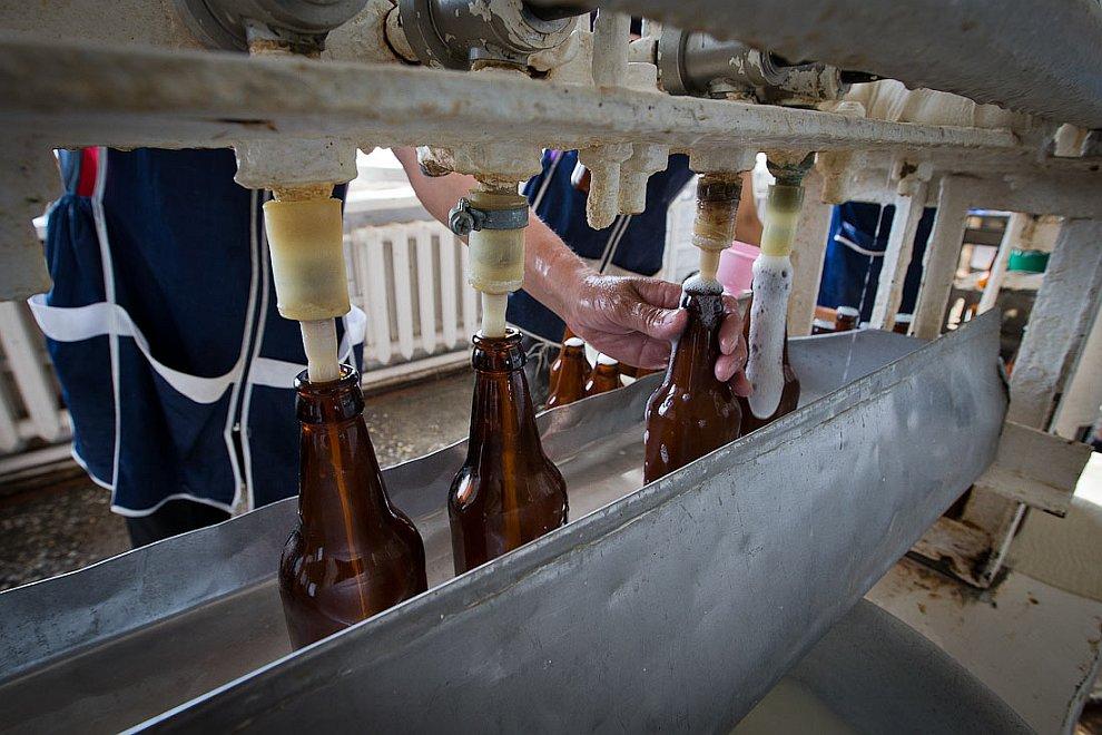С помощью нехитрого приспособления бутылки закупоривают металлическими крышками: