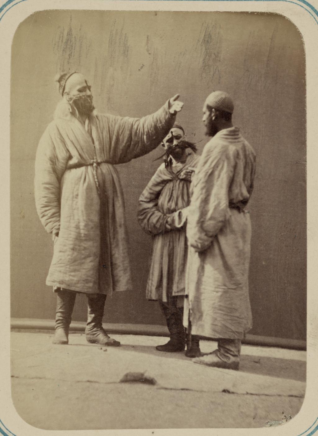 Трое мужчин, в том числе двое масхара-базу, или артистов развлекательного жанра, с раскрашенными лицами и накладными бородами