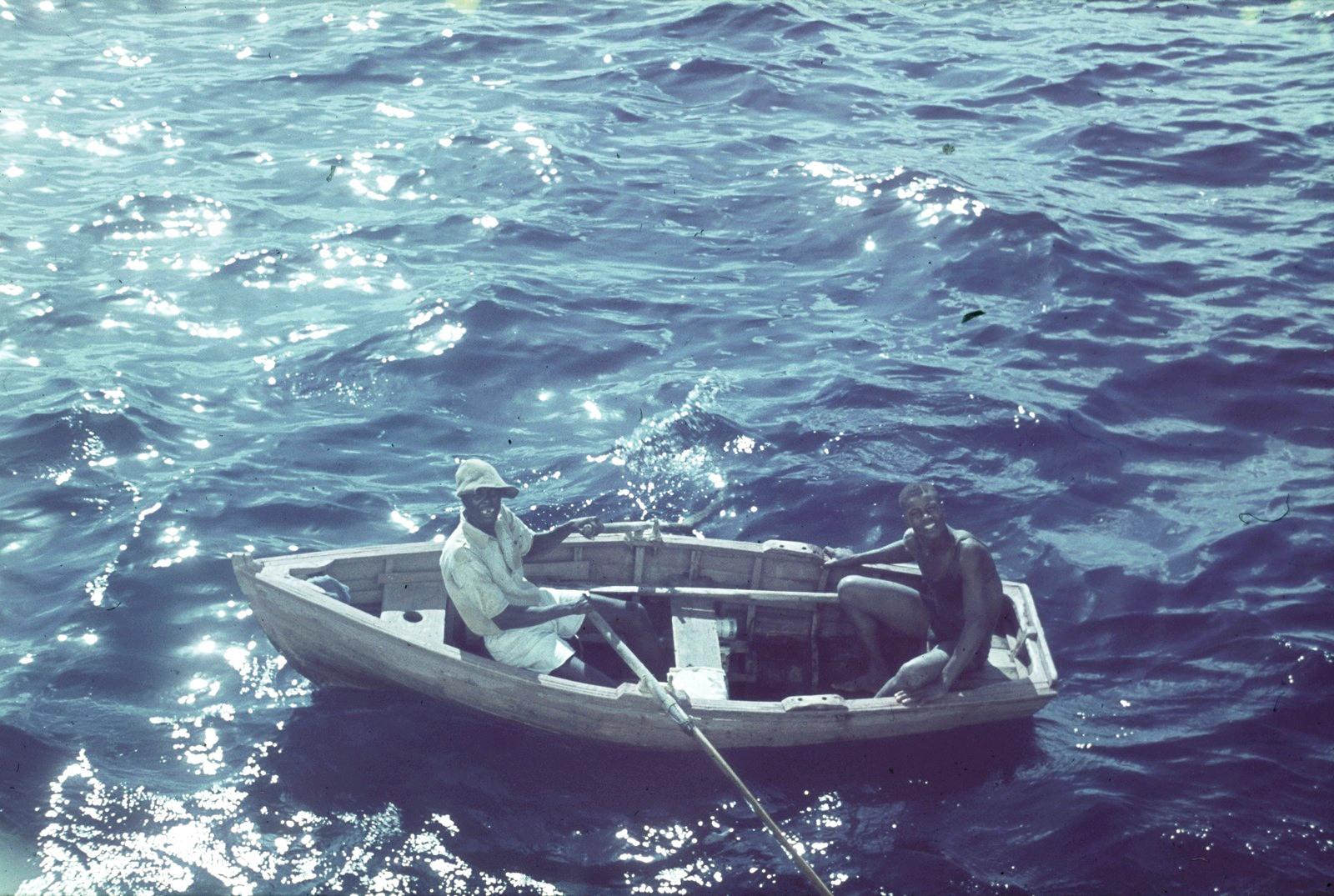 Гаити. Два местных жителей на лодке. Вид с пассажирского судна