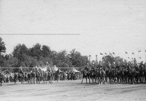 Уланский полк проходит церемониальным маршем по плацу во время парада.