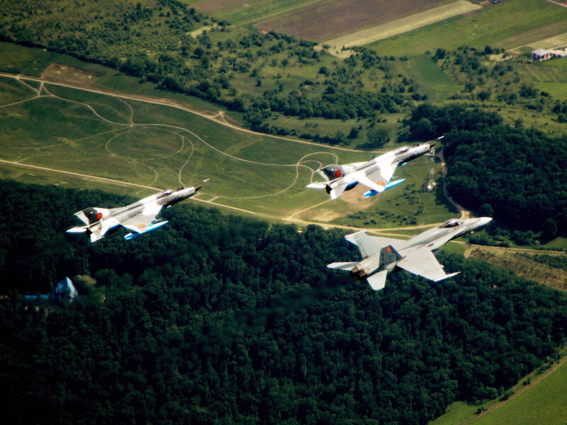 A CF-18 Hornet flies in formation with two Romanian MiG-21 LanceR aircraft on 22 May 2014 near Câmpia Turzii, Romania, where Canadian Air Task Force is participating in NATO reassurance measures.Photo: LS Alex Roy, 3 Wing BagotvilleBN2014-1011-02