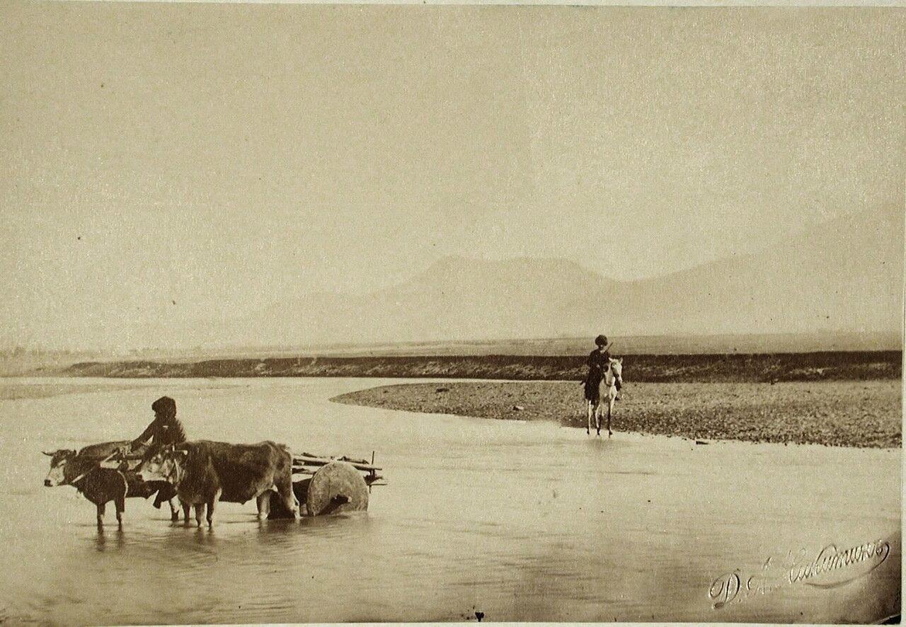 Местный житель с повозкой, запряжённой быками, переходит вброд реку Карс-чай