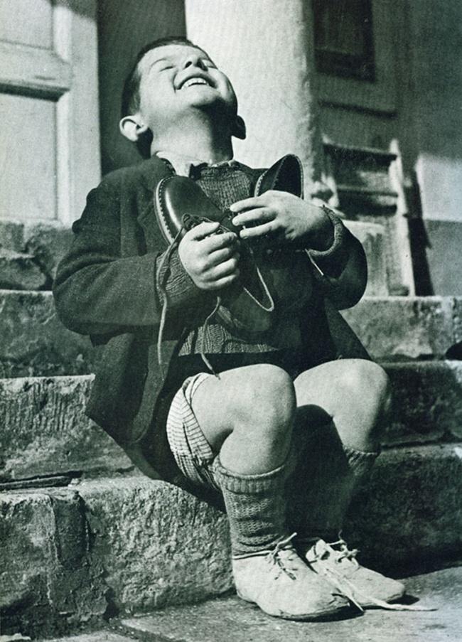 Австралийский мальчик радуется новым ботинкам вовремя Второй мировой войны.