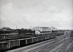 Поезда на железнодорожных путях на станции; на втором плане- здание вокзала.