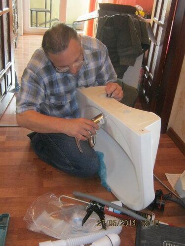Рукодельник крепит смеситель к раковине
