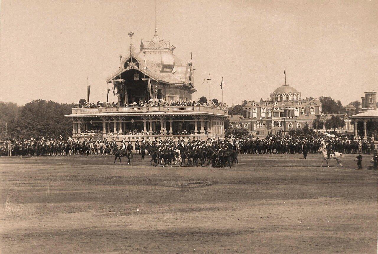 Прохождение одного из конных полков церемониальным маршем во время парада на Ходынском поле; на втором плане - императорский павильон, справа - Петровский путевой (подъездной) дворец