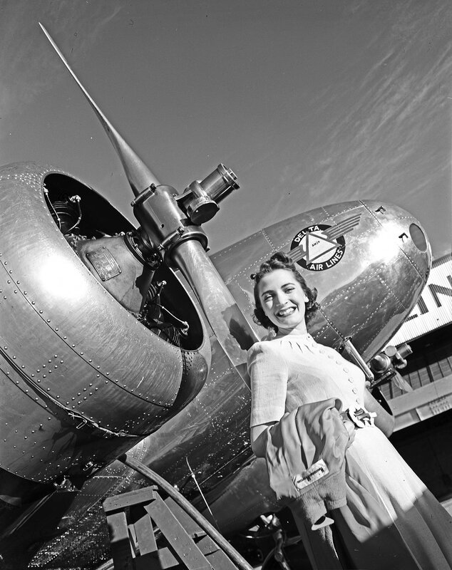 A female model standing next to a Lockheed Model 10B Electra, owned by Delta Air Lines, at Dallas Love Field Airport. March 1940