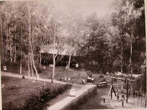 Дети в саду училища во время прогулки.