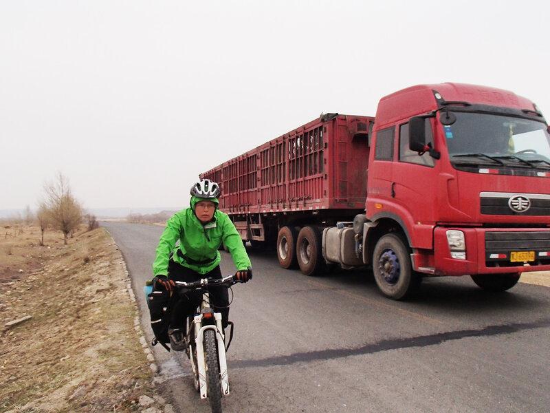китайская фура объезжает велосипедиста