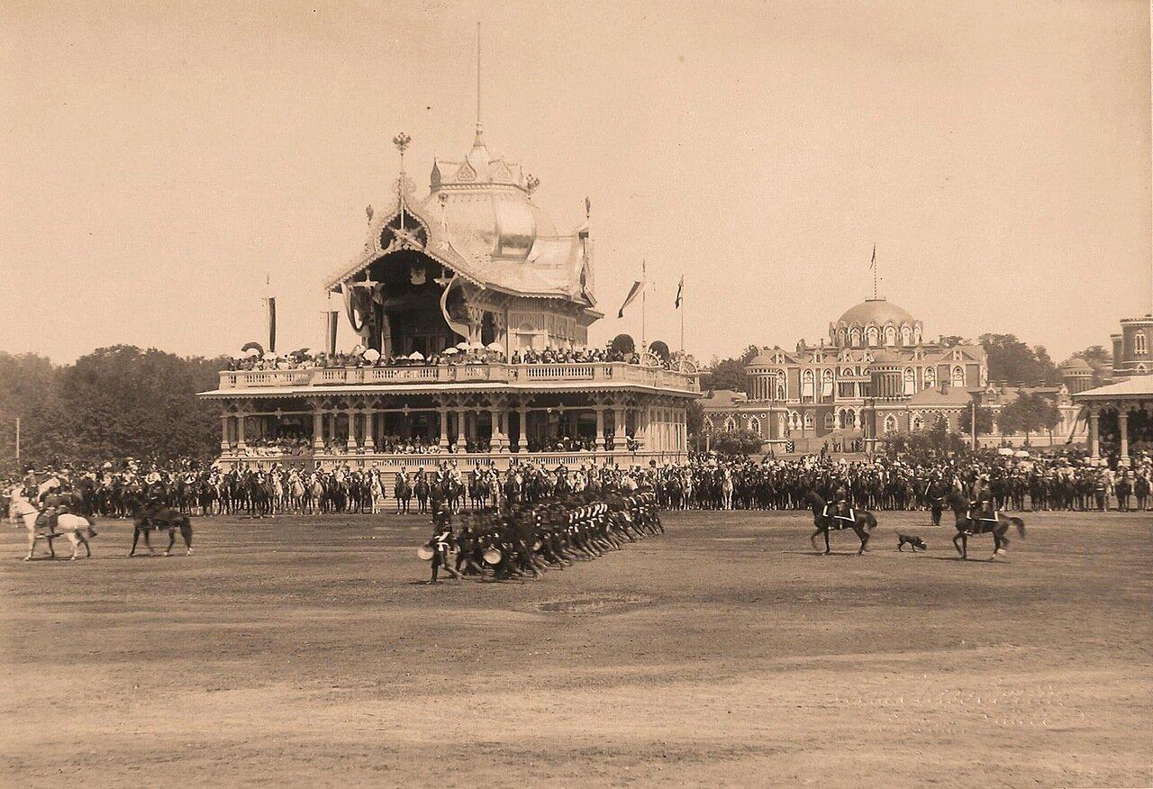 Прохождение пехотинцев церемониальным маршем во время парада на Ходынском поле; на втором плане - императорский павильон, справа - Петровский путевой дворец