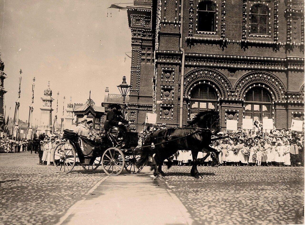 Учащиеся начальных школ и гимназий приветствуют прибывших императора Николая II и императрицу Александровну на Воскресенской площади у здания Городской думы