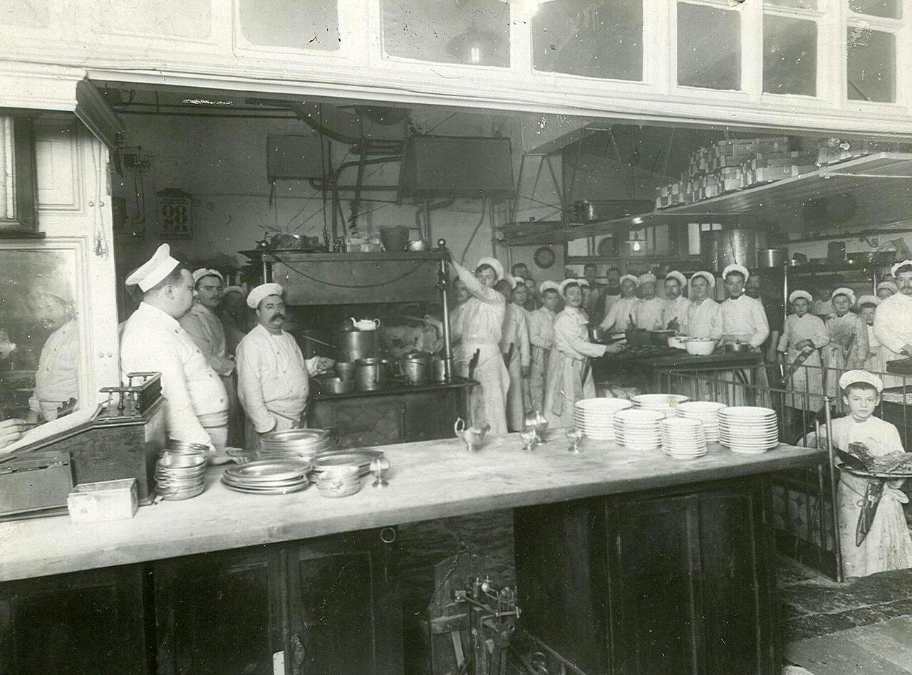 Повара и их помощники за приготовлением пищи в кухне ресторана