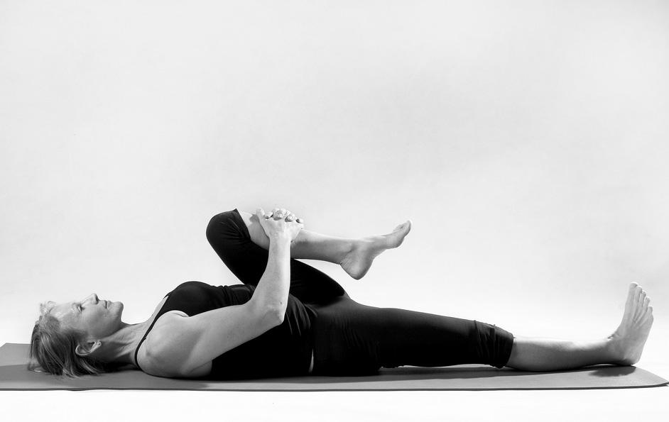 Лежа на спине, прижмите одно колено к груди, а другую ногу держите прямо. Сделайте несколько глубоки