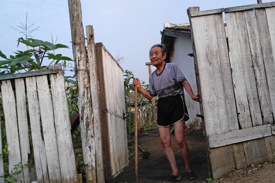 6. Пожилой мужчина выглядывает со своего двора в Туманганге