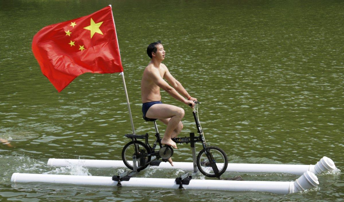6. Лю Ваньюн создал этот импровизированный велосипед, который держится на плаву благодаря пластиковы