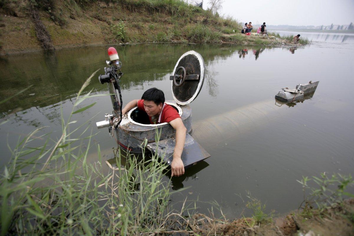 27. Тао Сянли выходит из своей самодельной субмарины после ее испытаний в озере.