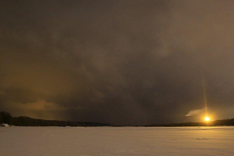 Зимний вид на юго-восток вдоль замёрзшей Вятки от городского пляжа.. Пасмурное небо, лес в Заречном парке, трубы и прожектора деревообрабатывающего предприятия