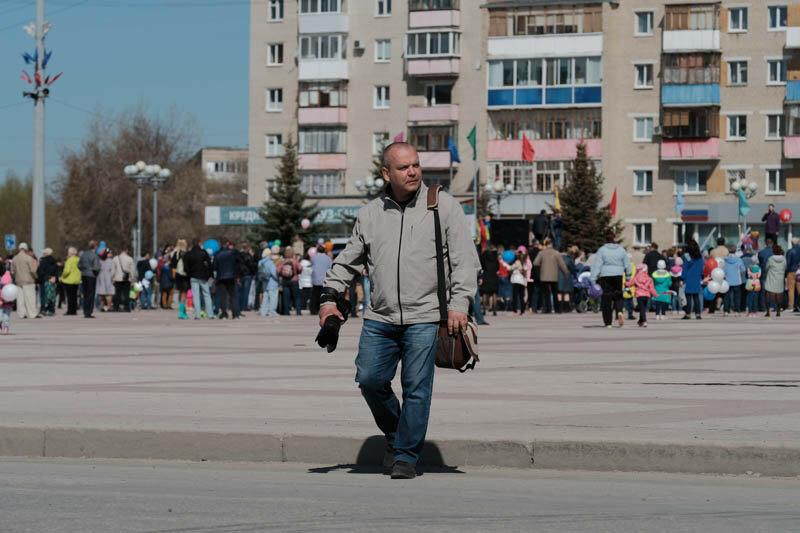 фотограф идет по улице с фотоаппаратом