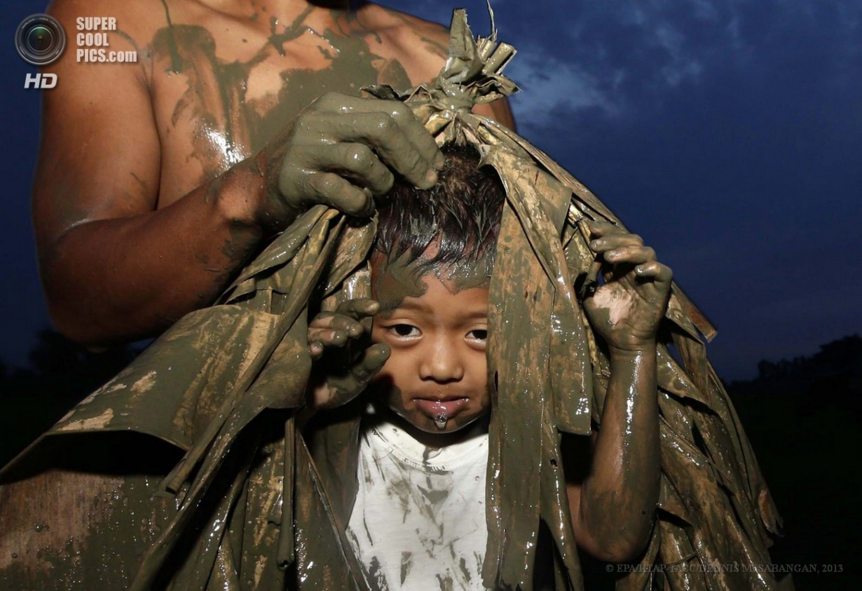 Филиппины. Алиага, Нуэва-Эсиха. 24 июня. Филиппинские католики покрывают друг друга грязью и оде