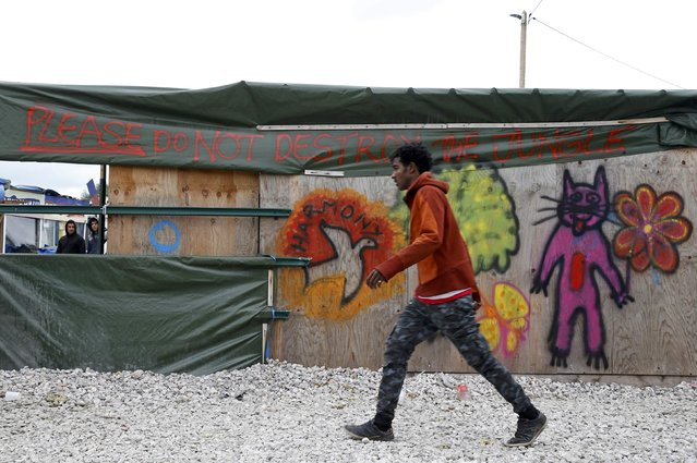 """A migrant walks past a shop with the message """"Please do not destroy the Jungle"""" in what is"""