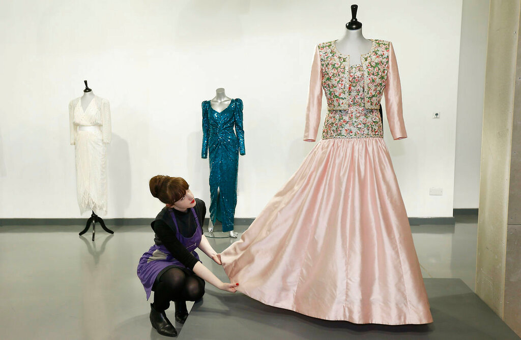 Assistant Lucy Bishop poses with a Catherine Walker Mughal-inspired pink slubbed silk evening gown and bolero worn by Diana, Princess of Wales, at Kerry Taylor Auctions in London
