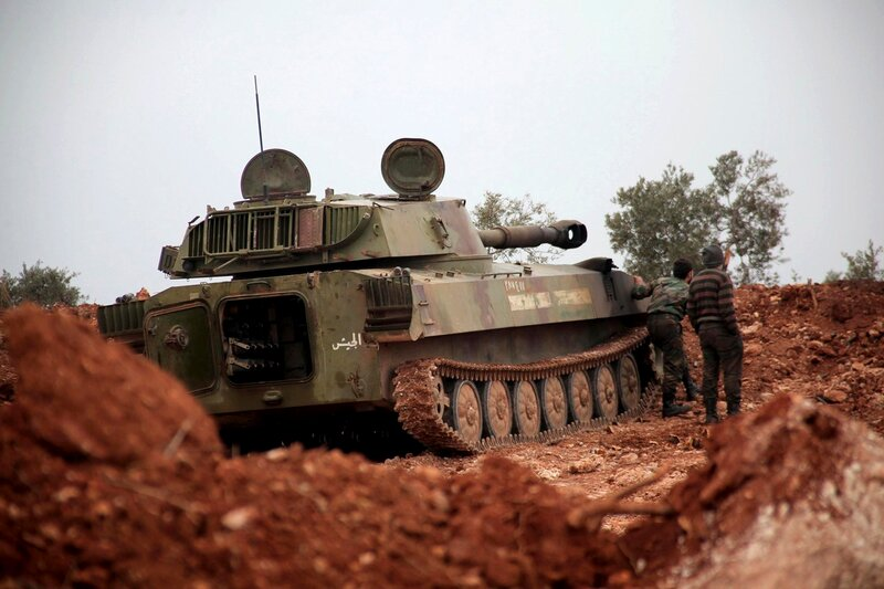 Syrian army soldiers loyal to Syria's President al-Assad stand by a tank in an operation to control the neighborhoods of Sheikh Lutfi and Marja in Aleppo