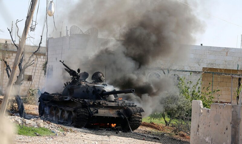 Smoke rises from a tank belonging to the Syrian government forces during clashes in the town of Morek