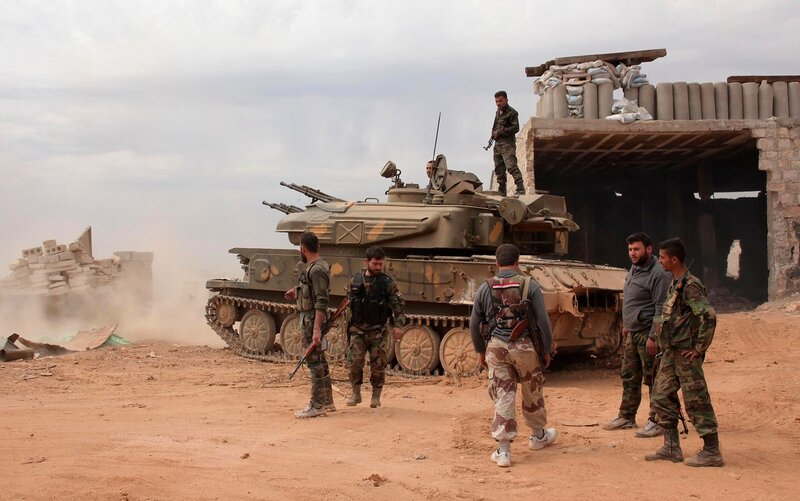 Syrian army soldiers loyal to Syria's President Bashar al-Assad hold their weapons as they stand near a tank in al-Maamel area in Aleppo's countryside