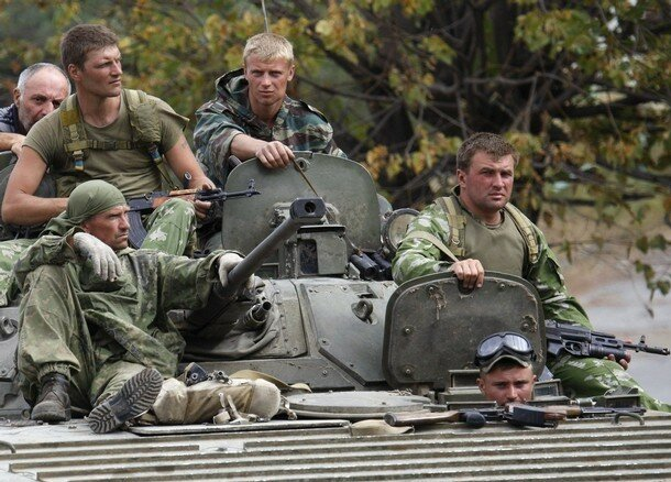 Russian soldiers sit on a military vehicle in the Georgian city of Gori