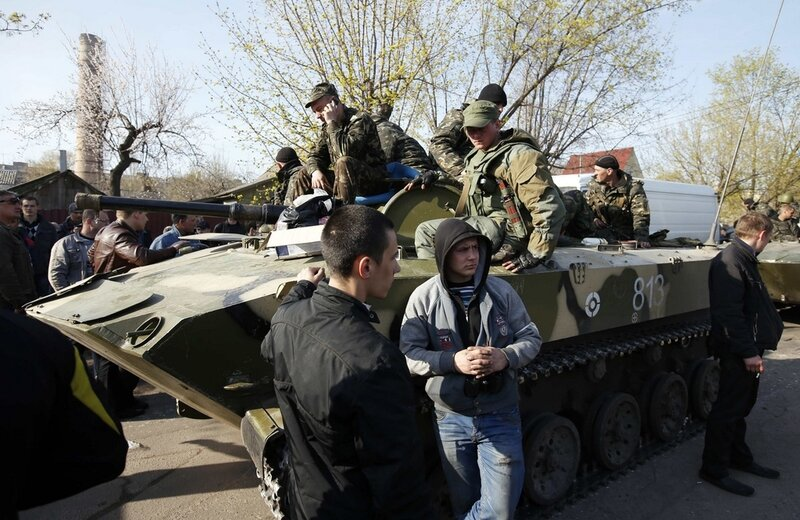 Ukrainian soldiers sit on an airborne combat vehicle surrounded by pro-Russia protesters in Kramatorsk