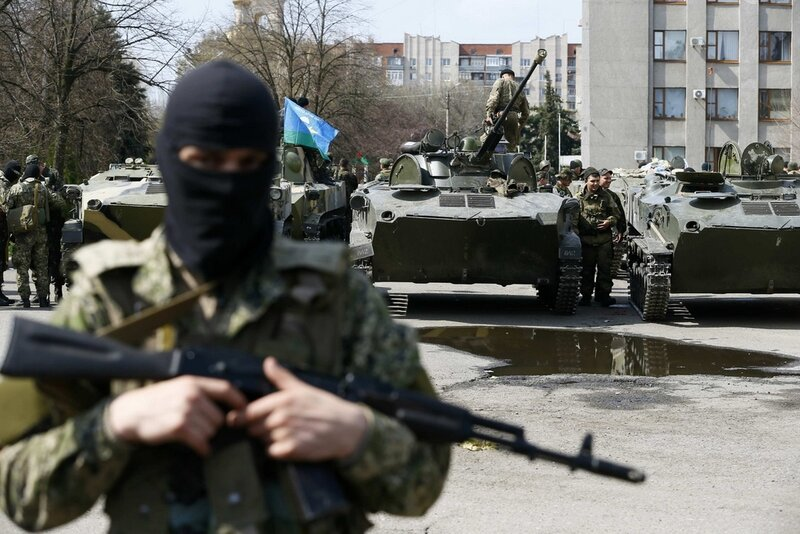 Armed men stand near armoured personnel carriers in Slaviansk