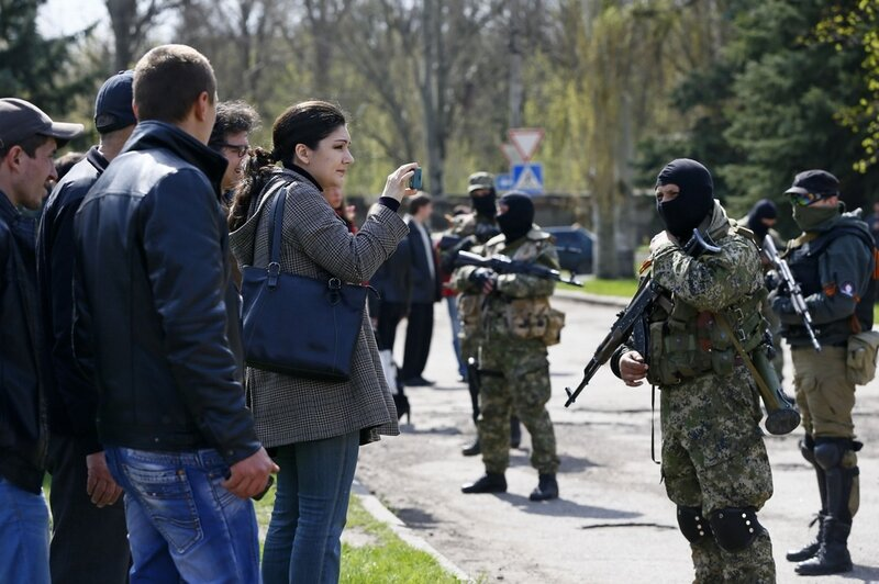 A woman takes pictures of armed men in Slaviansk