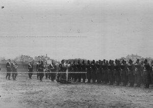 Император Николай II в сопровождении свиты и духовенства обходит 1-ую Уральскую его величества казачью сотню, выстроенную для парада полка .