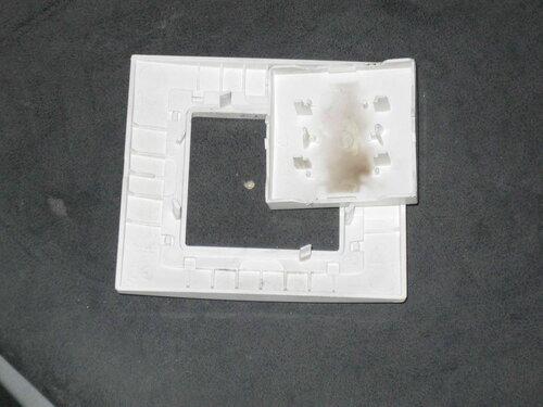 Фото 3. Демонтированные рамка и клавиша выключателя. Крупный план. На обратной стороне клавиши видна копоть.