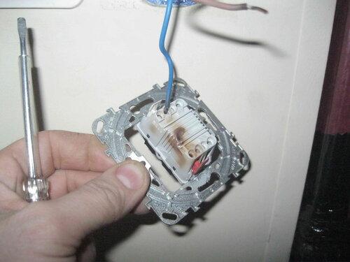 Фото 7. Демонтаж механизма выключателя (в сборе с суппортом). Пластмасса механизма оплавилась и потемнела, изоляция проводов несёт следы систематического перегрева.