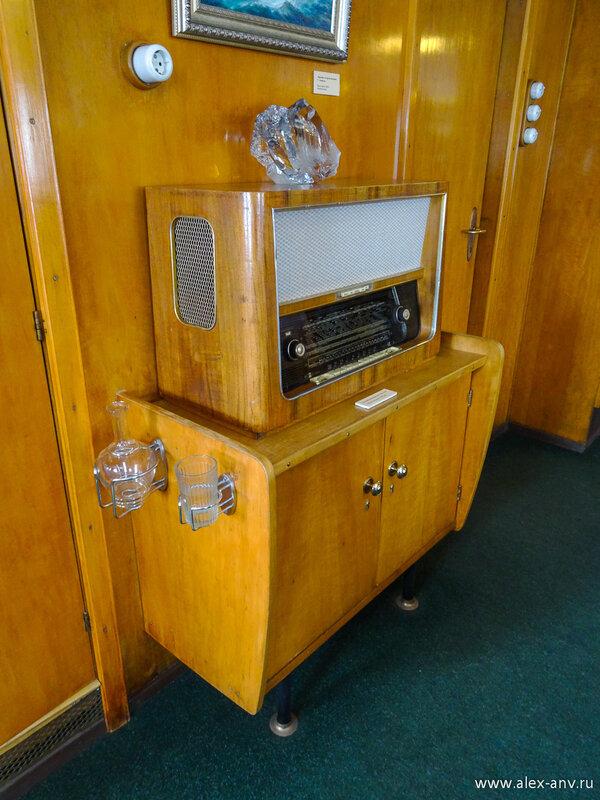 Каюта капитана богато украшена по моде пятидесятых годов прошлого века. В гостиной видное место занимает радиоприёмник. Отдельно умиляют графин со стаканом...