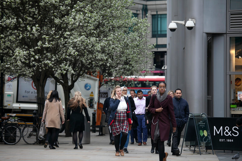 The crowd  are walking in the Spitalfield market area against a backdrop of flowering trees