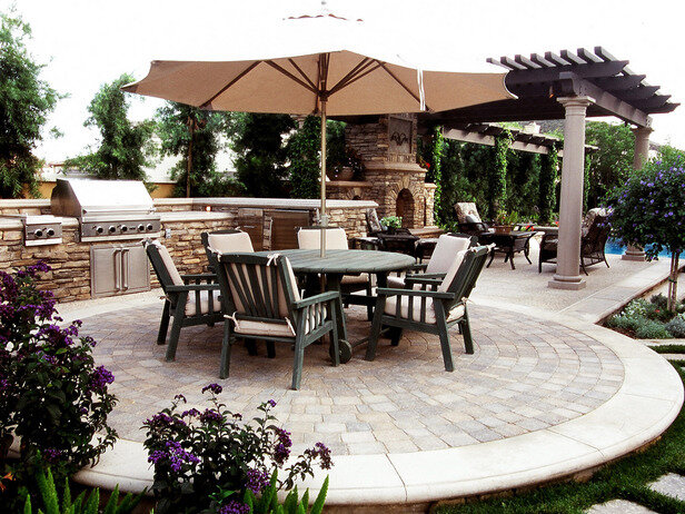 Outdoor room with sitting area and umbrella shade, grill with countertop, circular paver design, and stone fireplace.