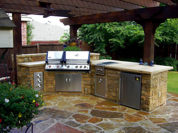 Outdoor kitchen with mini fridge, storage and countertop, and pergola with ceiling fan.