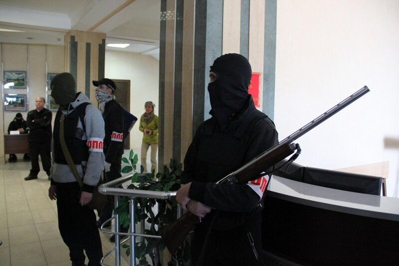 Men in uniform, one of them with a gun, wearing hand bandages of so-called Slavic patriotic organization reading: Oplot ( Stronghold), stand in a city administration building in the city of Donetsk, Eastern Ukraine, Wednesday, April 16, 2014. Kiev authori