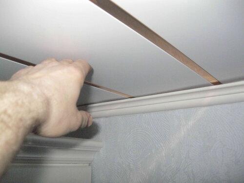Фото 31. За счёт частых лёгких постукиваний по широкой рейке (создав вибрацию), электрик добивается взаимного выравнивания потолочных реек (устранения «ступеньки» на плоскости потолка).