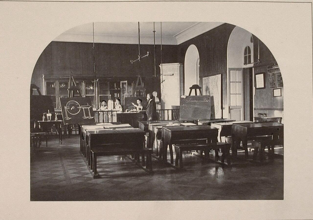 Воспитанницы и учитель в кабинете физики во время подготовки к урокам