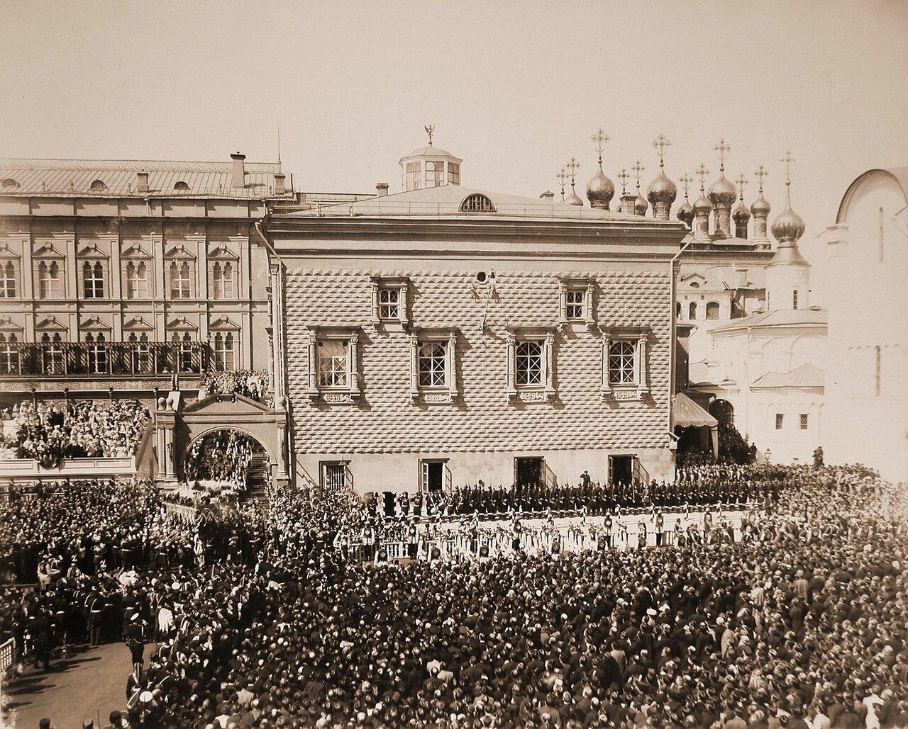 Император Николай II и императрица Александра Федоровна, шествующие под балдахином, в сопровождении свиты направляются в Успенский собор; по ступеням Красного крыльца спускается взвод лейб-гвардии Кавалергардского полка