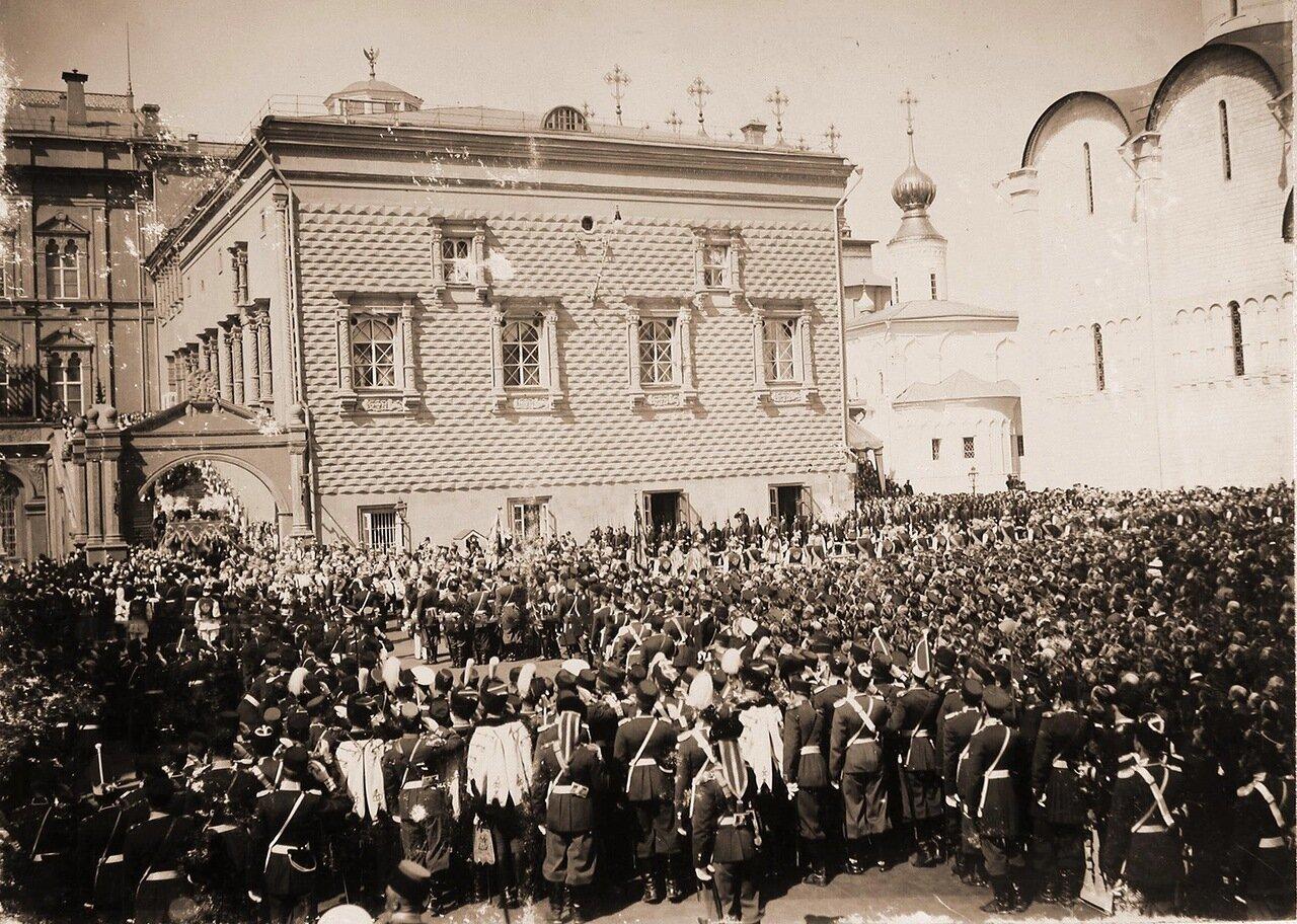 Нижние чины шефских частей и зрители на Соборной площади Кремля наблюдают шествиеих императорских величеств под балдахином от Красного крыльца Грановитой палаты к Успенскому собору в день торжественной коронации