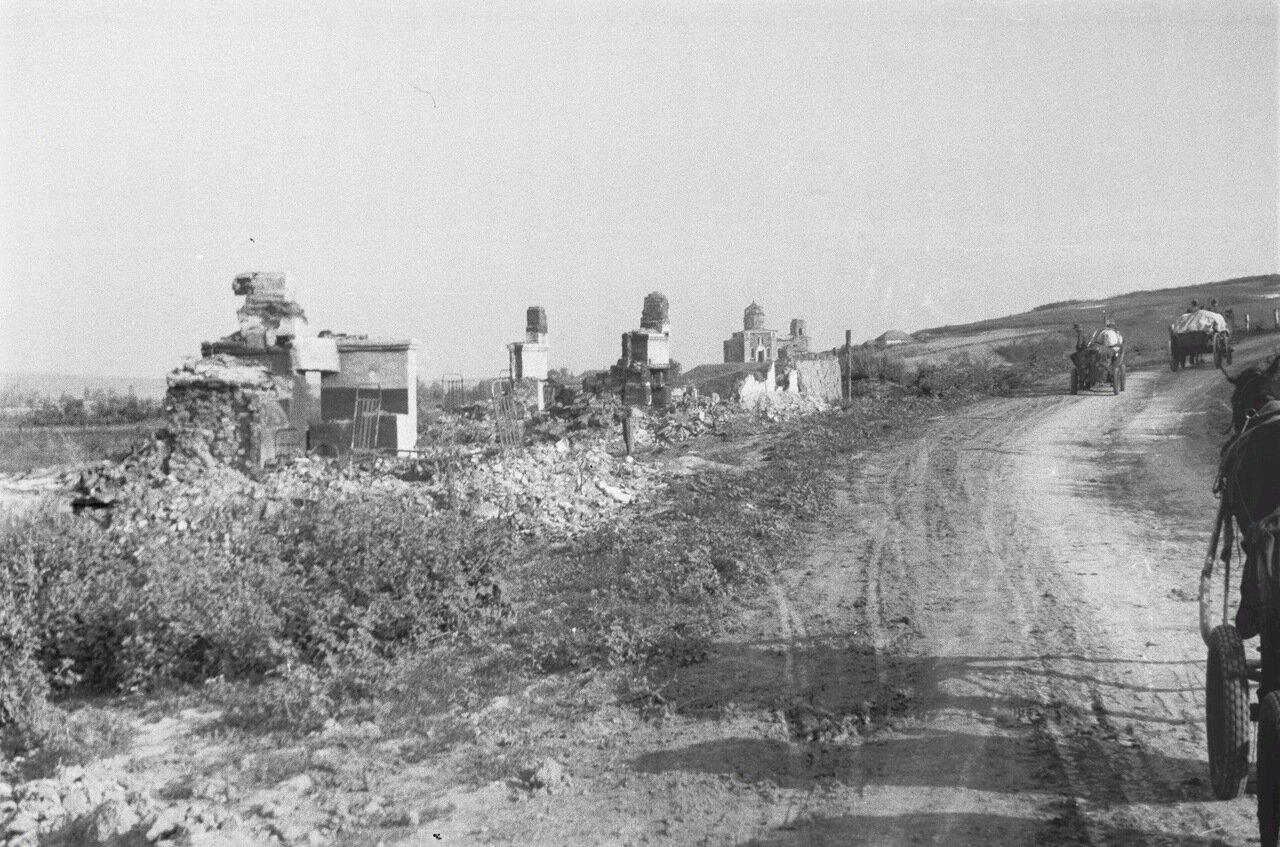 Белгородская область. Разрушенные дома вдоль проселочной дороги. Виден немецкий обоз. На заднем плане село с церковью