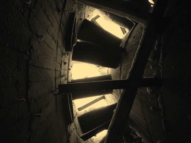 Вид со дна бетонного стакана на небо через переплетение труб заброшенной градирни