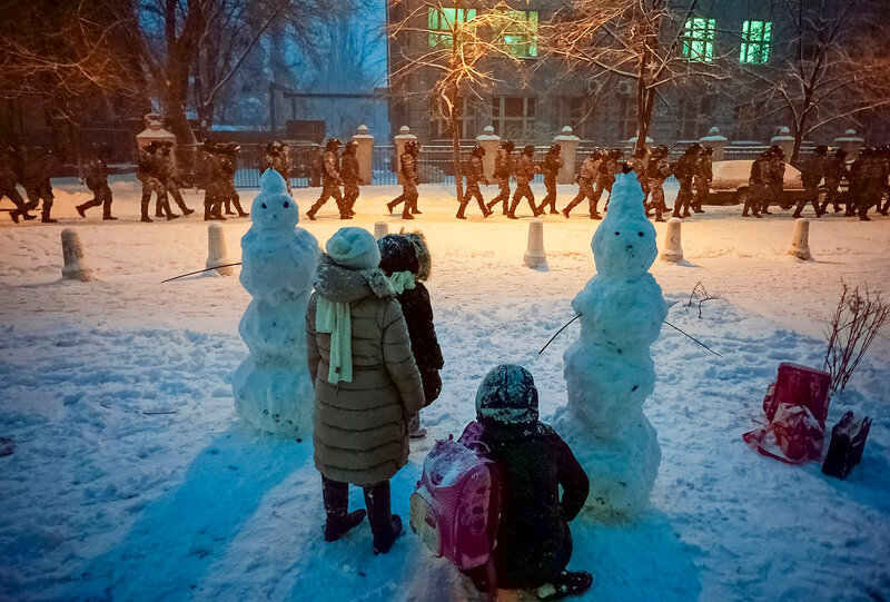 Children look on as riot police go to block a street near the presidential administration building during a gathering of supporters of EU integration in Kiev