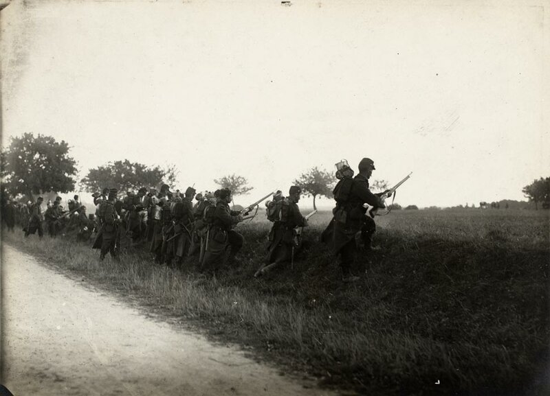 Des fantassins, en tenue de mobilisation et armés de fusils modèle Berthier 1907, exécutent un assaut.
