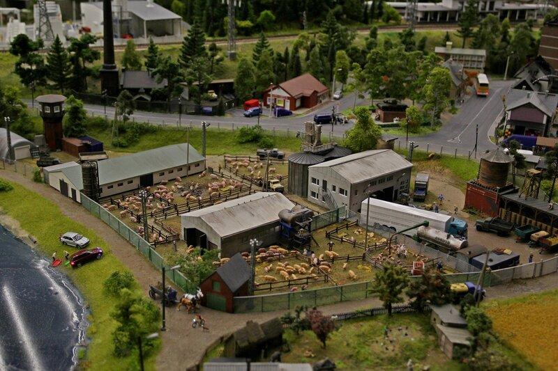 Гранд макет: скотный двор свинофермы - хрюшки в загонах, запряженная лошадьми телега, машины на берегу реки